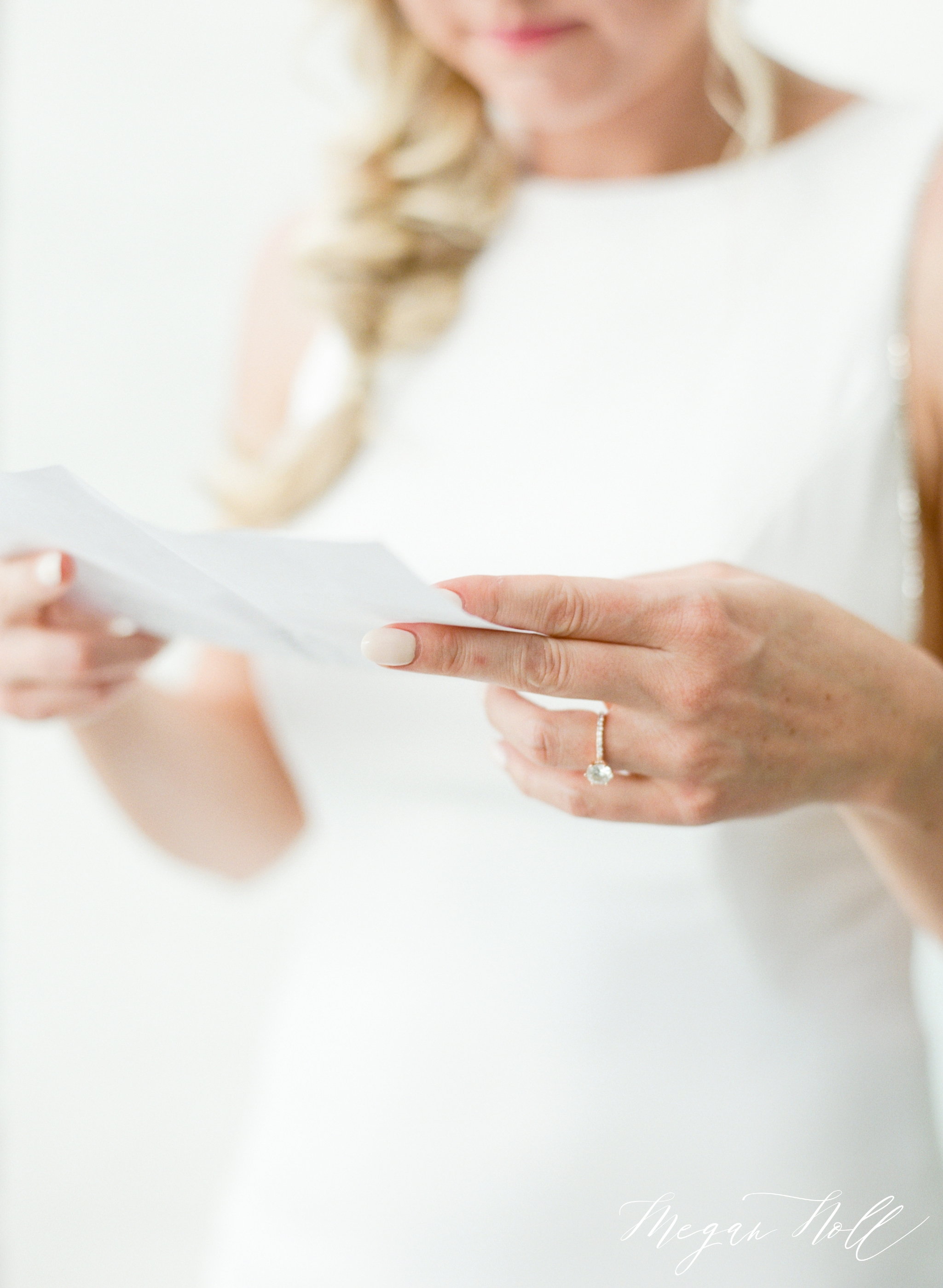 Close up of bride holding letter from groom